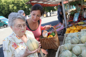 caregiver assisting senior woman to buy foods