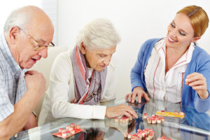 caregiver assisting the seniors in their activity